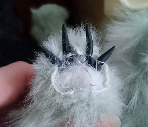 Sewing bear claws onto bear paws